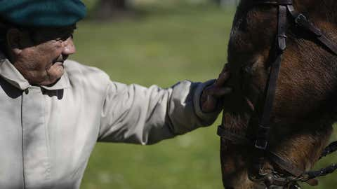 Oscar Villafane pets Coco the horse at the San Jose Home for seniors where he lives in Tandil Argentina, Wednesday, Sept. 15, 2021. The residence took in the horse during the COVID-19 lockdown to cheer up their elderly residents. (AP Photo/Natacha Pisarenko)
