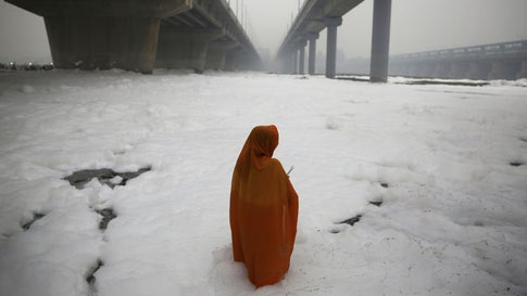 n Hindu devotee performs rituals in Yamuna River, covered by a chemical foam caused by industrial and domestic pollution, during the Chhath Puja festival in New Delhi, India, on Saturday, Nov. 2, 2019. The ancient festival expresses gratitude to the sun god for sustaining life on Earth. (AP Photo/Altaf Qadri)