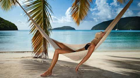 Woman relaxing in a hammock on a tropical beach, Maho Bay, St. John