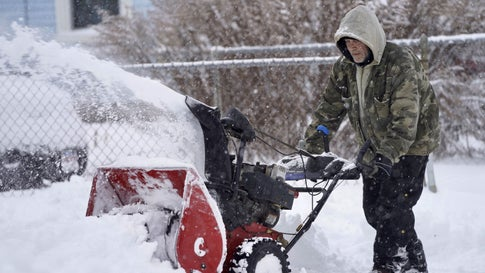Keith Standring clears snow for The Alternative Living Center in Pittsfield, Mass., following an overnight snowstorm Monday, Dec. 2, 2019. (Ben Garver/The Berkshire Eagle via AP)