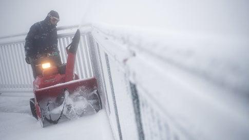 ARCHIV - 26.08.2018, Bayern, Grainau: Ein Mann fährt mit einem Schneepflug auf dem Gipfel der Zugspitze über die Aussichtsplattform. Foto: Sven Hoppe/dpa +++ dpa-Bildfunk +++