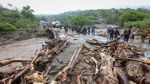 Passengers from stranded vehicles stand next to the debris from floodwaters, on the road from Kapenguria, in West Pokot county, in western Kenya Saturday, Nov. 23. Kenya's interior minister says dozens of people have been killed in mudslides, after heavy rains caused floodin in western Kenya. (AP Photo)