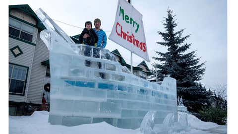 Donnie White and his four year-old son Mateo pose with the ice ship Donnie built on their front yard using frozen blocks of ice from a nearby pond in Red Deer, Alta., Wednesday, Jan. 10, 2018. (Jeff McIntosh/THE CANADIAN PRESS)