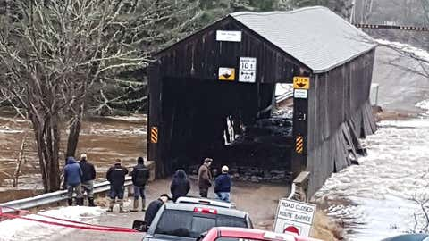 Residents check on the damage to the Bell Bridge in Hoyt, N.B. in this undated handout photo. New Brunswick's stock of historic and picturesque covered bridges continues to decline, with the province acknowledging it cannot save one ravaged by ice and flood waters over the weekend. (Debbie McCann/THE CANADIAN PRESS/HO *MANDATORY CREDIT*)