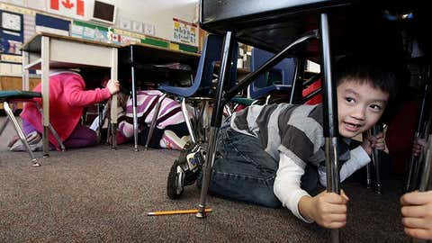 Grade one student Joseph Kim takes cover under his desk during an earthquake drill at Hollyburn Elementary School in West Vancouver. (Darryl Dyck/CP)
