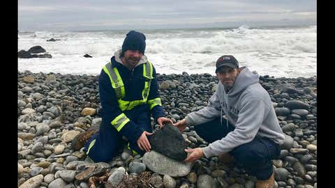 Graham and Joey with the lump of coal they discovered after it washed ashore on March 5, 2018 during the tidal surge (Photo courtesy of White Point Beach Resort)