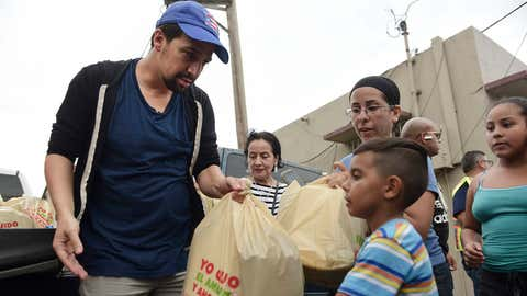Actor and composer of Puerto Rican descent Lin Manuel Miranda distributes food to victims of Hurricane Maria in La Placita de Güisin, in Vega Alta, Puerto Rico, Tuesday, Nov. 7, 2017. (AP Photo/Carlos Giusti)