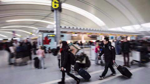 People carry luggage at Pearson International Airport in Toronto on Dec. 20, 2013. (Mark Blinch/THE CANADIAN PRESS)
