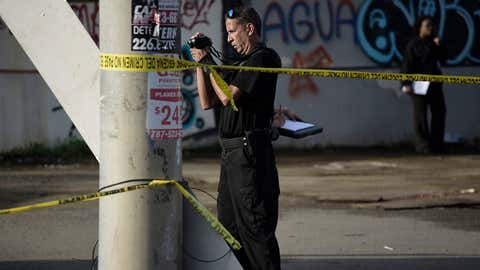 A forensic worker photographs a crime scene where a man was found fatally shot, in San Juan, Puerto Rico, Thursday, Jan. 11, 2018. Thirty-two people have been slain in Puerto Rico in the first 11 days of the year, double the number killed over the same period in 2017. If the surge proves to be more than just a temporary blip, January could be the most homicidal month on the island in at least two years, adding a dangerous new element to the island's recovery from Hurricane Maria. (AP Photo/Carlos Giusti)
