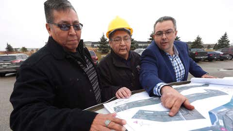 From left, Daryl Redsky, consultation officer, Chief Erwin Redsky, both of Shoal Lake 40 First Nation, and Phil Cesario, design project manager at PM Associates Ltd. go over the final design drawings for Freedom Road, an all-weather road which will connect the reserve to the Trans Canada highway, in Winnipeg on November 25, 2016. The final phase of construction is about to begin on an all-weather road for an isolated Indigenous community separated from the outside world more than a century ago. Freedom Road will provide a year-round landlink between the Shoal Lake 40 First Nation in northwestern Ontario and the Trans-Canada Highway in Manitoba. (John Woodsv/THE CANADIAN PRESS)