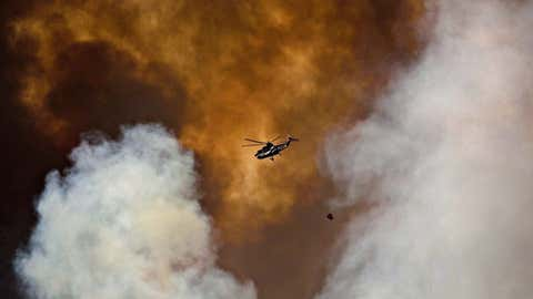 A helicopter battles a wildfire in Fort McMurray Alta, on Wednesday May 4, 2016. A report on lessons learned from the Fort McMurray wildfire recommends improved prevention along with better disaster management and evacuation planning. (Jason Franson/THE CANADIAN PRESS)