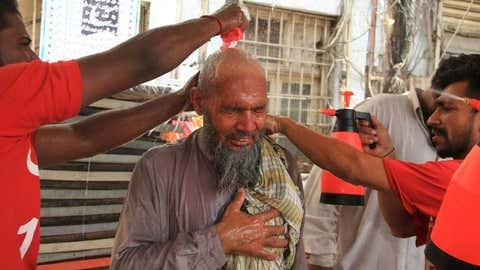 Un grupo de voluntarios refrescan a un anciano en Karachi, en Pakistán, el martes, cuando la temperatura alcanzó los 42 grados. IMRAN ALI / AFP / GETTY
