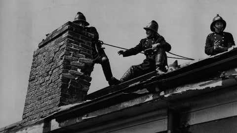 Tres bomberos aseguran una chimenea en la que ha impactado un rayo. EVENING STANDARD / GETTY