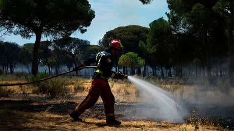 Un bombero sofoca el fuego en el camping Palya, en Mazagon (Huelva), en junio de 2017. CRISTINA QUICLER / AFP / GETTY