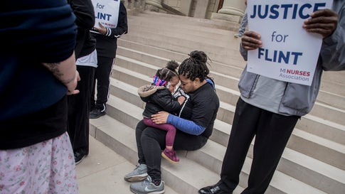"""Flint resident Takisha Moller consoles her 3-year-old daughter Destinee Wilson in the middle of the protest on the steps of the Capitol Building during a rally on the five-year anniversary of the Flint water crisis on Thursday, April 25, 2019, in Lansing, Michigan. Moller became pregnant with Desintee in 2014 before giving birth to her in 2015. Throughout her pregnancy, Moller drank unfiltered Flint tap water. """"I boiled water to give her baths, and I boiled her bottles, not knowing that I was further poisoning her. And the result of that: She's 3 years old, she's the size of maybe a one-and-a-half-year-old,"""" Moller said. (Jake May/MLive.com/The Flint Journal via AP)"""
