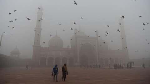 8 novembre 2017. Des visiteurs traversent la cour de la mosquée Jama Masjid, située dans la vieille ville. Le taux de pollution est 30 fois plus élevé que le taux conseillé par l'Organisation mondiale de la Santé (OMS). Les écoles sont restées fermées pour l'occasion et les habitants sont nombreux à se couvrir le visage pour se protéger.  Sajjad Hussain/AFP/Getty Images