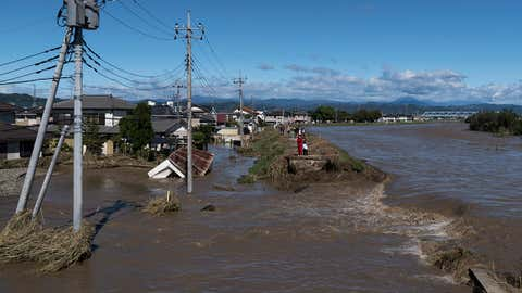 SANO, JAPAN - OCTOBER 13: A couple stands on a collapsed river bank of the Akiyama River following the passage of Typhoon Hagibis on October 13, 2019 in Sano, Tochigi Japan. At least five people are reported dead and many others are missing after Typhoon Hagibis, one of the most powerful storms in decades, swept across the country. (Photo by Tomohiro Ohsumi/Getty Images)