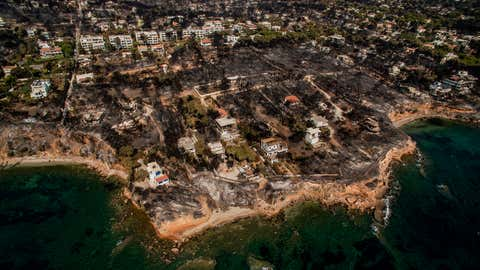 An aerial view shows a burnt area following a wildfire in the village of Mati, near Athens, on July 26, 2018. - Greece was counting the cost on July 26 of its deadliest wildfires in living memory, as emergency crews searched incinerated homes and vehicles for the missing after at least 81 people were confirmed to have died. (SAVVAS KARMANIOLAS/AFP/Getty Images)
