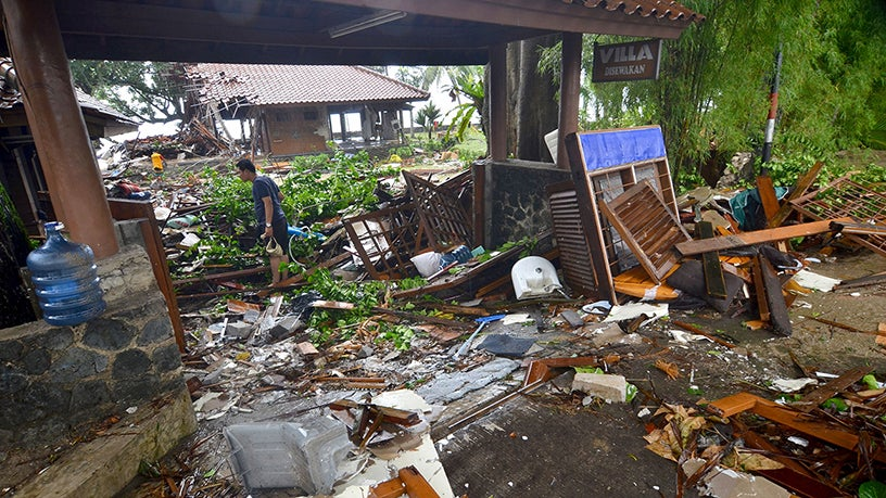 A man walks amid debris from damaged buildings in Carita on Sunday, December 23, 2018, after the area was hit by a tsunami following an eruption of the Anak Krakatoa volcano. (Ronald/AFP/Getty Images)