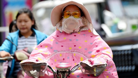 A citizen covering her face with sun protective clothing to escape heat rides on the road on May 23, 2019, in Luoyang, Henan Province of China. The highest temperature in Luoyang reaches above 98 degrees Fahrenheit on Thursday. (VCG/VCG via Getty Images)