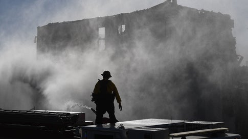 Firefighters hose down a burning house during the Tick Fire in Agua Dulce near Santa Clarita, Calif., on Oct. 25, 2019. California firefighters battled through the night to contain a fast-moving wildfire driven by high winds that was threatening to engulf thousands of buildings. Around 40,000 people were told to flee the Tick Fire, which was raging across 4,000 acres (1,600 hectares) just north of Los Angeles. (Mark Ralston/AFP/Getty Images)