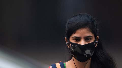 "A woman wearing a protective face mask walks along a street in smoggy conditions in New Delhi on Nov. 4, 2019. Millions of people in India's capital started the week on Nov. 4 choking through ""eye-burning"" smog, with schools closed, cars taken off the road and construction halted. (Jewel Samad/AFP via Getty Images)"