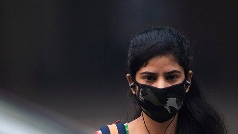 """A woman wearing a protective face mask walks along a street in smoggy conditions in New Delhi on Nov. 4, 2019. Millions of people in India's capital started the week on Nov. 4 choking through """"eye-burning"""" smog, with schools closed, cars taken off the road and construction halted. (Jewel Samad/AFP via Getty Images)"""