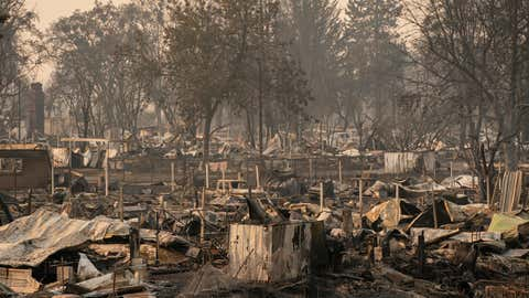 Damaged homes and cars are seen in a mobile home park destroyed by fire on Sept. 10, 2020, in Phoenix, Ore. Hundreds of homes in the town have been lost due to wildfire. (David Ryder/Getty Images)
