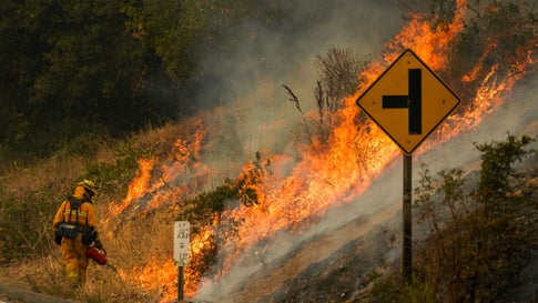 Firefighter uses a drip torch during a firing operation during the Glass Fire slowly creep across a clearing along Silverado Trail (CA-29) on Tuesday, Sept. 29, 2020, in Calistoga, Calif. (Kent Nishimura / Los Angeles Times via Getty Images)