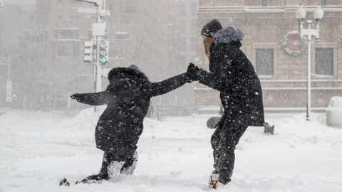 A woman helps her boyfriend stand up after slipping on the sidewalk on December 17, 2020 in Boston, Massachusetts.  The Gail winter storm brought more than a foot of snow Wednesday night to the Northeast and Thursday.  (Scott Eisen / Getty Images)