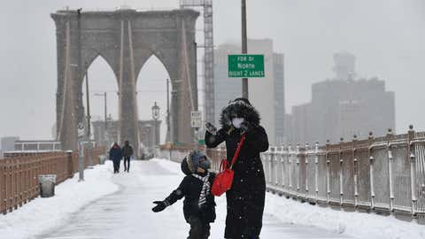 A woman and child play in the snow on the Brooklyn Bridge in New York, on Feb. 18, 2021. (Angela Weiss/AFP via Getty Images)