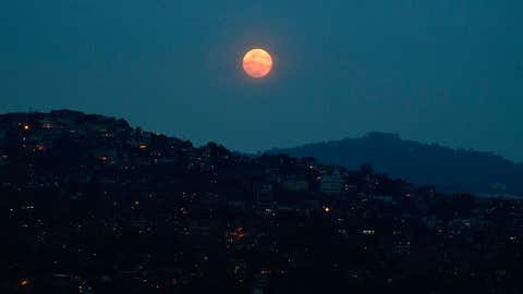 """The full """"Super Pink Moon"""" is seen over the Petare neighborhood in Caracas, Venezuela, on April 26, 2021. (Federico Parra/AFP via Getty Images)"""