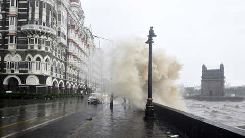 A motorists drive through a waterlogged road amidst heavy rains in Mumbai on May 17, 2021, as Cyclone Tauktae, packing ferocious winds and threatening a destructive storm surge, bears down on India, disrupting the country's response to its devastating COVID-19 outbreak. (Imtiyaz Shaikh/Anadolu Agency via Getty Images)