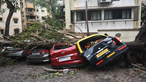 Cars are crushed by a fallen tree following heavy rainfall in Mumbai, India, on May 18, 2021. The Maharashtra state capital was largely spared from any major damage as Cyclone Tauktae, the most powerful storm to hit the region in more than two decades, came ashore in neighboring Gujarat state late Monday. (Imtiyaz Shaikh/Anadolu Agency via Getty Images)
