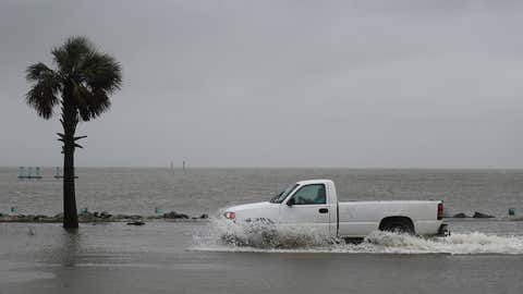 BAYOU LA BATRE, ALABAMA - SEPTEMBER 15:  A driver navigates along a flooded road as the outer bands of Hurricane Sally come ashore on September 15, 2020 in Bayou La Batre, Alabama. The storm is threatening to bring heavy rain, high winds and a dangerous storm surge from Louisiana to Florida. (Photo by Joe Raedle/Getty Images)