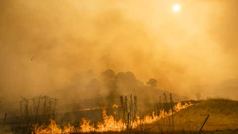 Flames and smoke from wildfires cover the landscape in California, U.S. Photographer: Philip Pacheco/Bloomberg