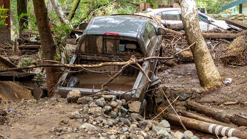 A pickup truck that was washed down a creek in Silverado Canyon in Silverado, Calif., sits wedged against a driveway with the creek flowing underneath following heavy rain early on Wednesday morning, March 10. 2021. The storm caused flash flooding and mud slides with cars and debris washed down the creeks as people that stayed behind try to dig out before more rain falls in the area. (Mark Rightmire/MediaNews Group/Orange County Register via Getty Images)