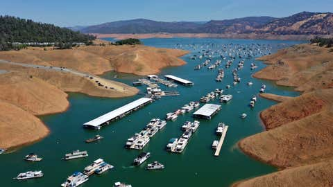 In an aerial view, houseboats sit anchored at the Bidwell Canyon Marina on Lake Oroville on June 1, 2021, in Oroville, Calif. As water levels continue to fall at Lake Oroville, officials are flagging houseboats that are anchored on the lake for removal to avoid being stuck or damaged. Lake Oroville is currently at 38% of normal capacity. According to the U.S. Drought Monitor, 16% of California is in exceptional drought, the most severe level of dryness. (Justin Sullivan/Getty Images)