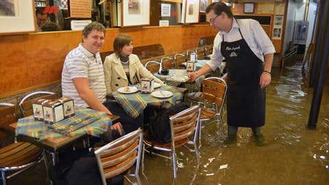 Dans un café de Venise, à l'automne 2012, un serveur et ses clients les pieds dans l'eau.