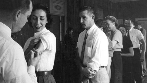 NOV 5 1957, NOV 6 1957; Denver Post Employees Get Flu Shots; Dr. A.E. James gives an influenza vaccination to Helen Hertz of the general advertising department of The Denver Post as a line of other employees await their turn. James Mills, personnel director, said 400 employes will be vaccinated.;  (Photo By Dean Conger/The Denver Post via Getty Images)
