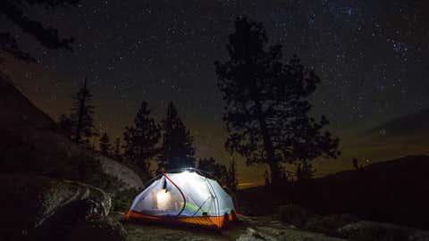 A light up tent under a full sky of stars.