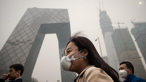 A woman wearing a protective pollution mask walks on a street in Beijing on March 20, 2017. - The last large coal-fired power plant in Beijing has suspended operations, with the city's electricity now generated by natural gas, the state news agency reported as smog enveloped the Chinese capital this past weekend. (Photo by NICOLAS ASFOURI / AFP)        (Photo credit should read NICOLAS ASFOURI/AFP/Getty Images)