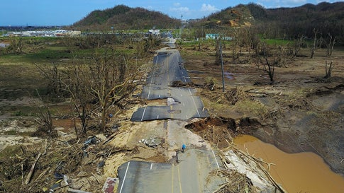 A man rides his bicycle through a damaged road in Toa Alta, west of San Juan, Puerto Rico, on September 24, 2017 following the passage of Hurricane Maria. Maria ransacked Dominica at Category 5 intensity, then was Puerto Rico's strongest hurricane strike since 1928. (RICARDO ARDUENGO/AFP/Getty Images)