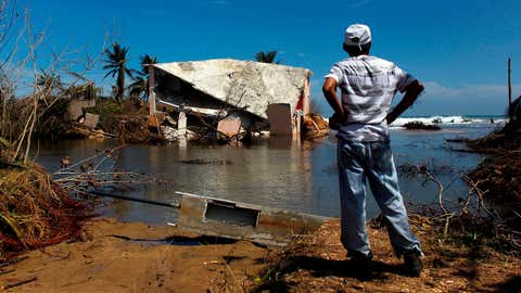 A man surveys a house that was washed away by heavy surf during the passing of Hurricane Maria in Manati, Puerto Rico, on October 6, 2017. A federal report has found that problems including staff shortages and lack of trained personnel slowed the U.S. government response to Hurricane Maria in Puerto Rico.  (Ricardo Arduengo/AFP/Getty Images)