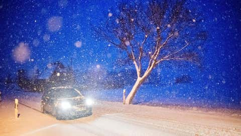 A car drives on a road covered with snow early on December 3, 2017, in the region of Hannover, central Germany. (JULIAN STRATENSCHULTE/AFP/Getty Images)