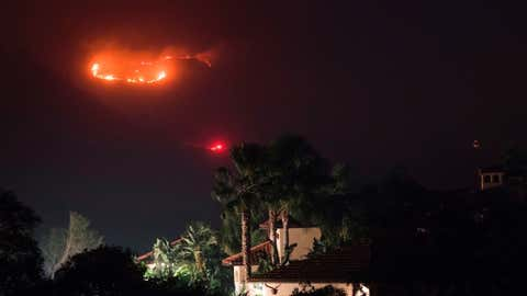 TOPSHOT - Fire burns in the hills behind a home at the Thomas Fire, December 16, 2017 in Montecito, California. (Photo by Robyn Beck / AFP)        (Photo credit should read ROBYN BECK/AFP via Getty Images)