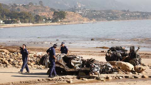 MONTECITO, CA – JANUARY 11, 2018: Alisha Kleinman, Steve Knight, and Brett Weideman, left to right, members of the US Coast Guard on Thursday morning inspect 2 crushed vehicles, a Hummer and a Honda that were found on the beach in Montecito, presumed victims of the flows in Montecito after a rainstorm sent mud and debris through Montecito neighborhoods. The Coast Guard is responsible to identify and clean up and hazardous material on the beach.  (Al Seib / Los Angeles Times)