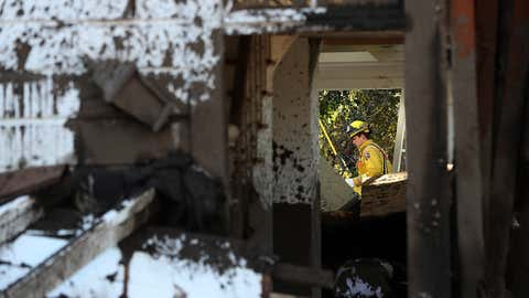 A Cal Fire firefighter inspects a home that was destroyed by a mudslide on January 12, 2018 in Montecito, Calif. 17 people have died and hundreds of homes have been destroyed or damaged after massive mudslides crashed through Montecito early Tuesday morning.  (Justin Sullivan/Getty Images)