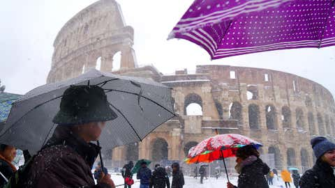 Tourists shed under umbrellas as they visit the ancient Colosseum during a snowfall in Rome on February 26, 2018.  (Vincenzo Pinto/AFP/Getty Images)