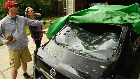 LOUISVILLE, CO - JUNE 19: Gregg Crouger, left, and his neighbor Loraine Benas look at the hail damage to Benas' Nissan Altima from a large hailstorm that raced through their neighborhood the night before on June 19, 2018 in Louisville, Colorado.  A severe hail storm hit their neighborhood with hail the size of large eggs that ripped through trees and destroyed many cars, rooftops and solar panels. More severe weather and afternoon thunderstorms are in the forecast for the rest of the week. (Photo by Helen H. Richardson/The Denver Post via Getty Images)